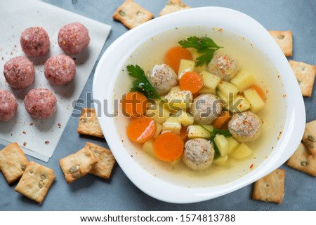Plate of meatball soup with crackers, high angle view over grey concrete background with raw uncooked meatballs