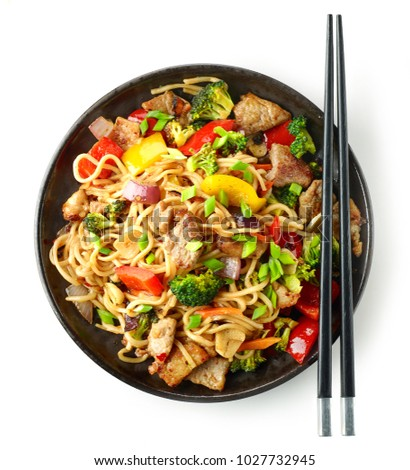 Plate of noodles with meat and vegetables isolated on white background, top view