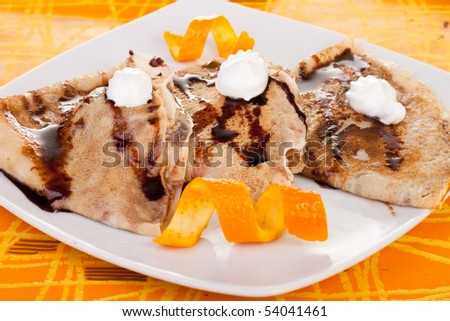 plate of pancakes decorated with orange peel and whipped cream