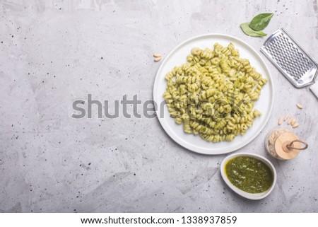 Plate of pasta with italian pesto sauce on gray concrete background. Horizontal orientation #1338937859