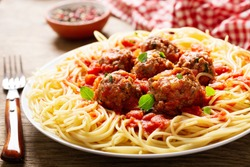 plate of pasta with meatballs on a wooden table