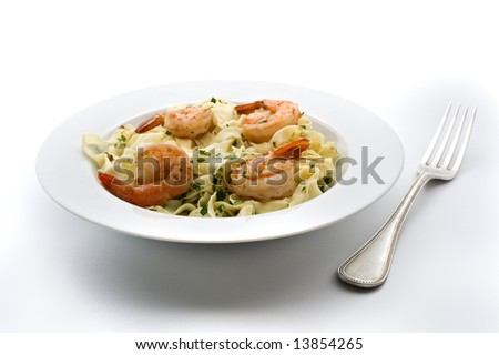 plate of pasta with shrimps and fork isolated on white