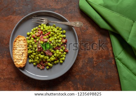 Plate of peas with ham and toast from above with rusty background and green silk cloth Foto stock ©