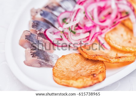 Detail Plate Of Pieces Of Herring With Fried Potato And Onion Close Up Image With Selective