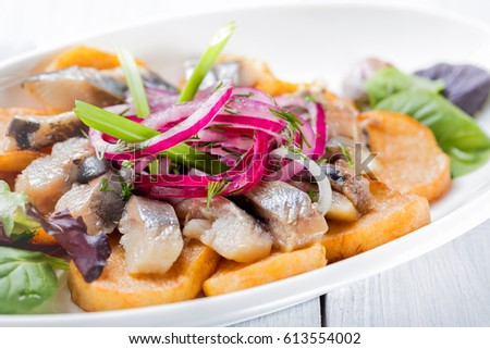 Detail Plate Of Pieces Of Herring With Fried Potato Onion And Salad Close Up Image