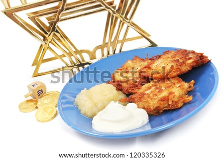 Plate of potato pancakes, a dreidel and Hanukkah gelt, and a menorah on white.