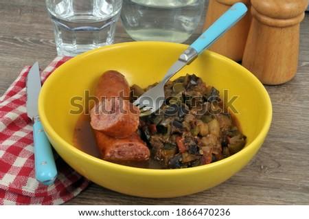 Plate of ratatouille with smoked sausage and fork close-up | Assiette de ratatouille avec une saucisse fumée et une fourchette en gros plan Photo stock ©