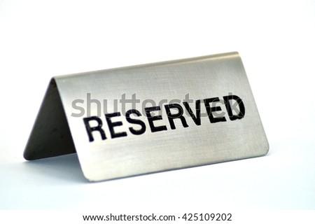 Plate of reservation of table of aluminum restaurant on white bottom. #425109202