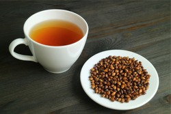 Plate of Roasted Barley with a Cup of Hot Japanese Barley Tea or Mugicha on Wooden Table