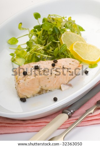 plate of salmon cooked with vegetables and lemon