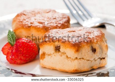 Plate of scones with strawberry decoration and fork