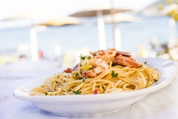 Plate of sea food, spicy pasta with shrimps served on the beach restaurant