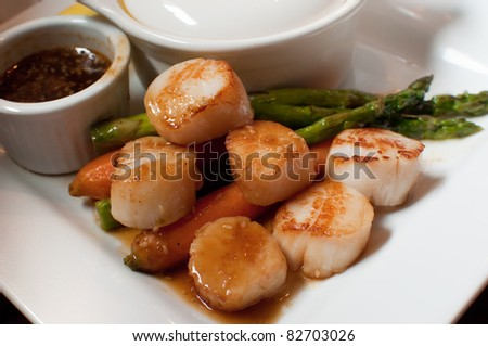 Plate of sea scallops in a teriyaki soy glaze with asparagus and carrots