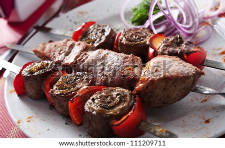 Plate of shish kebab arranged on table.