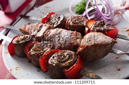 Plate of shish kebab arranged on table.