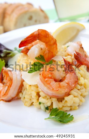 Plate of Shrimps Risotto garnished with fresh parsley, Parmesan cheese, glass of white wine and bread.