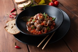Plate of snails with spicy tomato sauce, typical Italian food