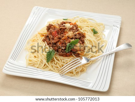 Plate of spaghetti with a herb-flavoured tomato sauce, topped with grated parmesan and a sprig of basil.