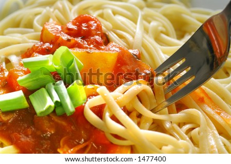 Plate of spaghetti with tomato sauce and a fork.
