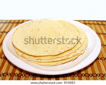 Plate of stacked tortillas on bamboo mat