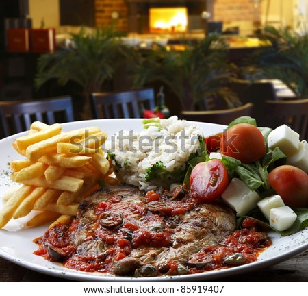 plate of steak with rice and salad