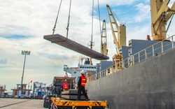 plate of steel slab being lifting by the ship crane, loading discharging operation for transfer the cargo shipment in export and import, works by stevedore labor in charge on jetty port terminal