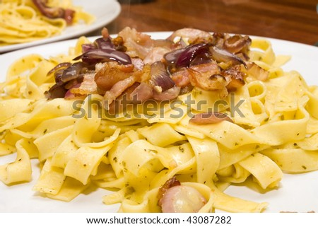 Plate of Tagliatelle pasta tossed in pesto and olive oil with fried bacon and red onion.