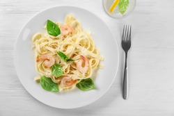 Plate of tasty pasta with shrimps on white wooden table, top view