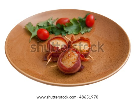 plate of three bacon wrapped scallops with cherry tomato garnish on a brown plate isolated on white