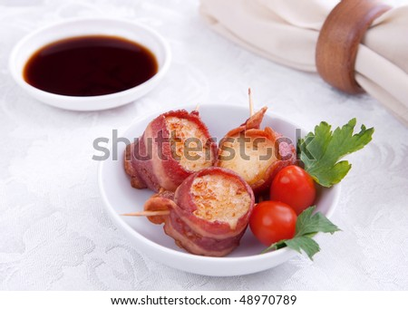 plate of three bacon wrapped scallops with cherry tomato garnish on a ...