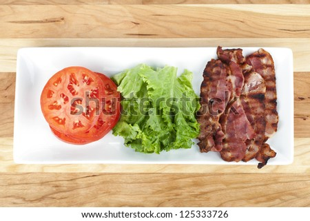 Plate of tomato, lettuce and crispy bacon over a wooden background - stock photo