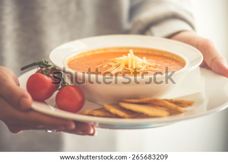 Plate of tomato soup served with cheese and toasts in hands. Toned picture