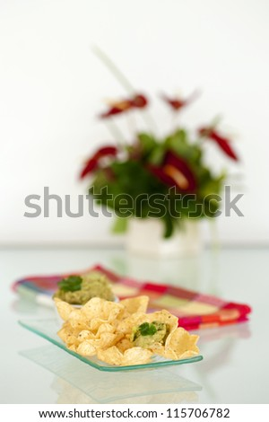 Plate of tortilla chips served with fresh made guacamole.