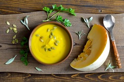 Plate of traditional pumpkin soup on a rustic background decorated by freshly picked garden herbs and pumpkin seeds