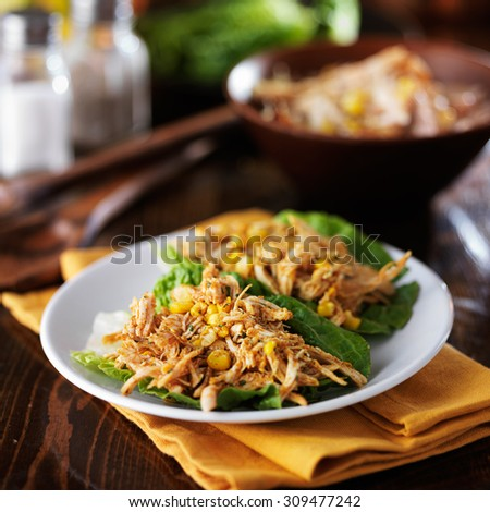 plate of two lettuce chicken wraps with spices and corn #309477242