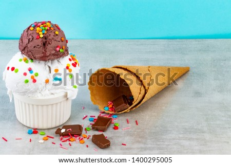 plate of vanilla and chocolate ice cream scoops swith sprinkles chocolate pieces and waffle cones on a blue background.