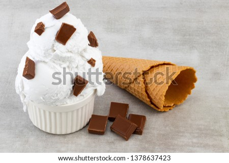plate of vanilla ice cream scoops, and chocolate pieces and waffle cones.