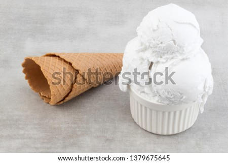 plate of vanilla ice cream scoops and waffle cones.
