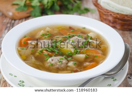 Plate of vegetable soup with meatballs on the wooden table closeup