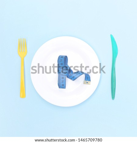 Plate with a centimeter, fork and knife on a blue background.