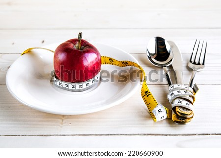 plate with apple measure tape, knife and fork. Diet food on wooden table