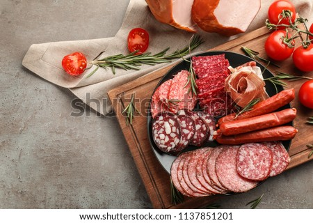 Plate with assortment of delicious deli meats on grey background