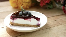 Plate with Blueberry Cheese Tart. Berries and Rosemary placed on top. Beautiful tasty dessert on the table. Enjoy fresh baked dessert in Coffee Shop. Closeup shot of little sweet decorative cake.