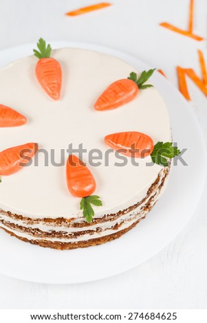 Plate with carrot sponge cake with little orange carrots and cream on white background