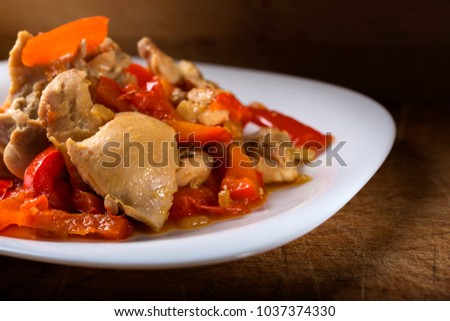 Plate with chicken stew with red pepper on wooden background #1037374330
