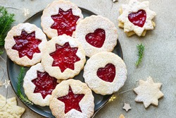 Plate with Christmas or New Year shortcrust cookies with red jam. Traditional festive Austrian cookies with jam. Linzer cookies.
