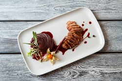 Plate with cooked meat. Sliced meat with decoration. Duck breast with sweet sauce. Delicacy of European cuisine.