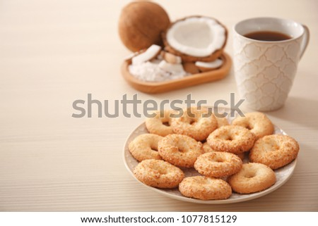 Plate with cookies and cup of tea on wooden background
