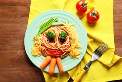 Plate with creative pasta for children on table