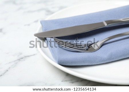 Plate with cutlery and napkin on marble table, closeup #1235654134